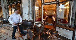 Nhân viên thu dọn bàn ghế trong quán Cafe Florian ở quảng trường Saint Mark, thành phố Venice hôm 8/3. Ảnh: AFP